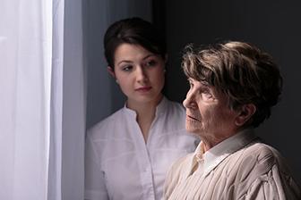 Bewohnerin mit Pflegepersonal, Seniorenzentrum, Pflegeimmobilien zur Kapitalanlage